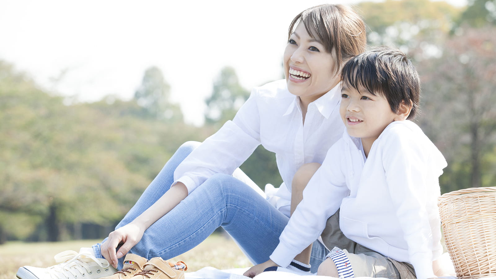 Asian lady and boy sitting in a park