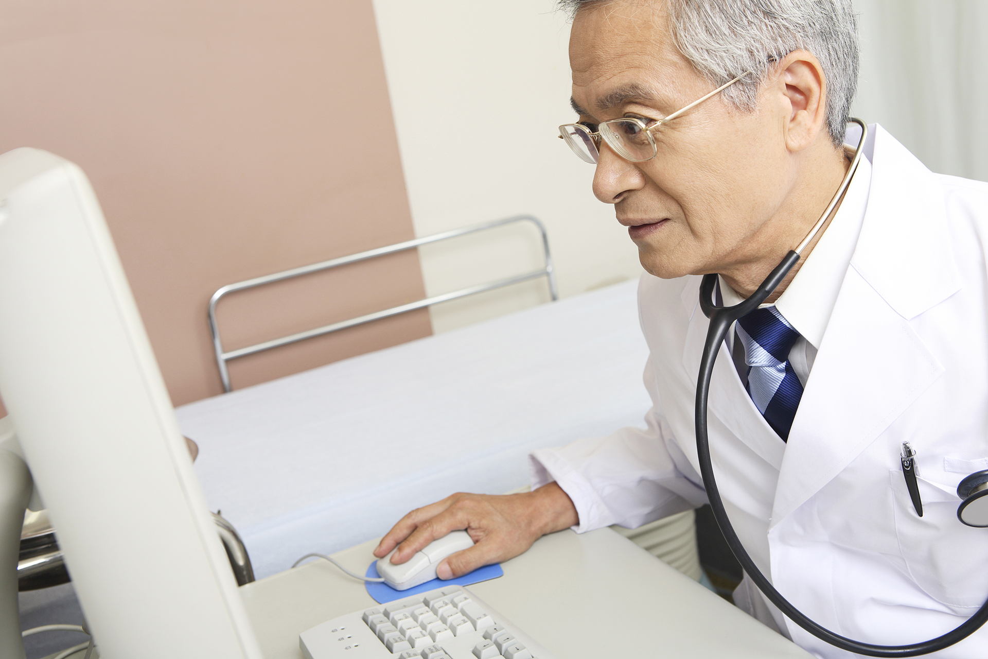 Asian doctor sitting at desk looking at computer screen